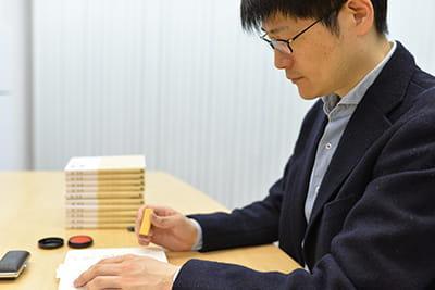 写真:自著の出版イベントで座右の銘印を使用する権さん